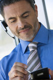 Businessman wearing telephone headset, using personal electronic organiser, close-up (tilt) Stock Photos