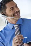 Businessman wearing telephone headset, using personal electronic organiser, smiling, close-up (tilt) Royalty Free Stock Photo