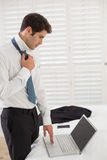 Businessman wearing tie while using laptop at a hotel room Royalty Free Stock Image
