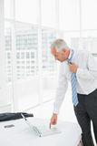 Businessman wearing tie while using laptop at a hotel room. Side view of a mature businessman wearing tie while using laptop at a hotel room Royalty Free Stock Photo