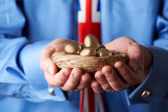 Businessman Wearing Union Jack Tie Holding Nest Of Golden Eggs Royalty Free Stock Images
