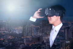Businessman wearing virtual reality goggles and night city view royalty free stock images