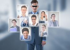 Businessman wearing Virtual reality headset interacting and choosing a person from group of people i. Digital composite of Businessman wearing Virtual reality Stock Photo