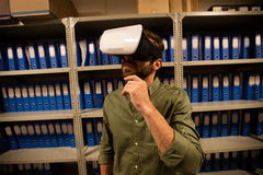 Businessman wearing VR glasses in file storage room. At workplace Royalty Free Stock Photo