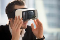 Businessman wearing vr glasses immersed in augmented reality. Stock Image