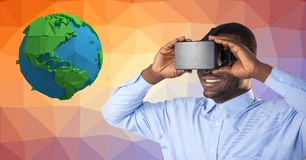 Businessman wearing VR glasses by low poly earth. Digital composite of Businessman wearing VR glasses by low poly earth Stock Photography