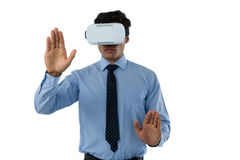 Businessman wearing vr glasses while using invisible interface. Against white background Stock Photo