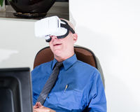 Businessman wearing VR headset, amazed. Amazed corporate executive wearing virtual reality headset Stock Photo