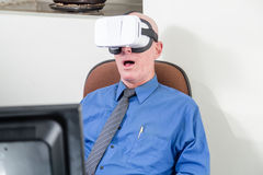 Businessman wearing VR headset, amazed. Amazed corporate executive wearing virtual reality headset Royalty Free Stock Images