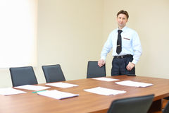 Businessman wearing white shirt stands near table Royalty Free Stock Photos