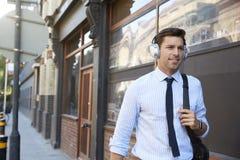 Businessman Wearing Wireless Headphones Walking To Work stock images