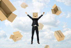 Businessman wears box on his head with funny face, lifts hands up and flying away Royalty Free Stock Images