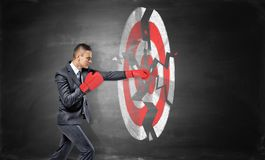 A businessman wears boxing gloves and breaks a chalk drawing of a round archery target. Success and failure. Reaching your goal. Break your record royalty free stock photography