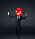 Businessman wears devil smiley face Stock Photo