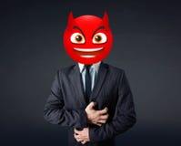 Businessman wears devil smiley face Stock Images