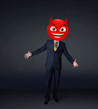 Businessman wears devil smiley face Stock Photo