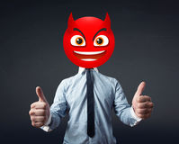 Businessman wears devil smiley face Royalty Free Stock Photo