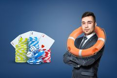 A businessman wears a life buoy on his shoulders and stands near gambling chips, cards and dice. Safe gambling. Loss insurance. Casino strategy stock images
