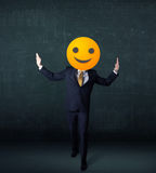 Businessman wears yellow smiley face Royalty Free Stock Photography