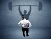 Businessman with weight lifting shadow Stock Photo