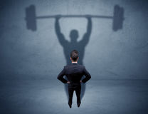 Businessman with weight lifting shadow Stock Photography