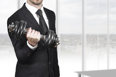 Businessman weightlifting in office Stock Images