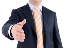 Businessman welcomes you. Businessman in blue suit greats you. He is giving a handshake to you Royalty Free Stock Images