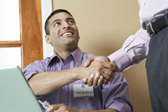 Businessman Welcoming Colleague. With a hand shake in office Royalty Free Stock Image