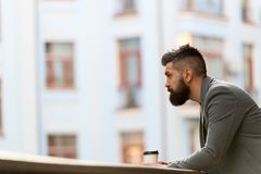 Businessman well groomed appearance enjoy coffee break out of business center urban background. Relax and recharge. Man. Bearded hipster drink coffee paper cup royalty free stock photography