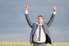 Businessman in a wheat field. Successful businessman farmer on the field with hands up Royalty Free Stock Photo