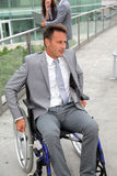 Businessman in wheelchair. Waiting for a taxi Royalty Free Stock Images