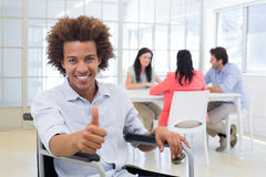 Businessman in wheelchair gives thumbs up to camera Stock Photography