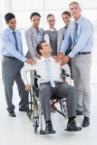 Businessman in wheelchair with his colleagues looking at camera Royalty Free Stock Photography