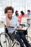 Businessman in wheelchair holding planner and smiling at camera Royalty Free Stock Photo