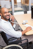 Businessman in wheelchair phoning and smiling at camera Royalty Free Stock Photography