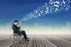 Businessman on wheelchair sending information Stock Photography