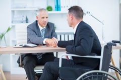 Businessman in wheelchair shaking hands with colleague Royalty Free Stock Images