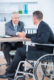 Businessman in wheelchair shaking hands with colleague Royalty Free Stock Image