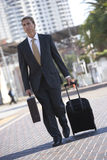 Businessman wheeling luggage in urban setting Royalty Free Stock Photos