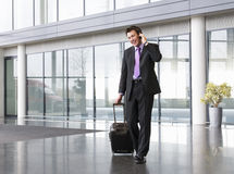 A businessman wheeling a trolley suitcase, talking on a mobile phone Stock Photography