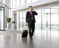 A businessman wheeling a trolley suitcase, talking on a mobile phone Stock Images