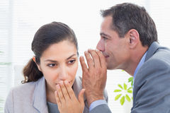 Businessman whispering something to his colleague. In an office Stock Image