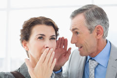Businessman whispering something to his colleague. In an office Stock Images