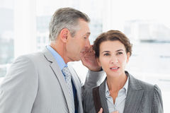 Businessman whispering something to his colleague Royalty Free Stock Photo