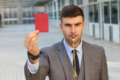 Businessman with whistle and red card.  stock photo