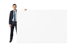 Businessman on white background holding a shoulder-height blank display board. Business and finance. Advertizing and promotion. Presentations Royalty Free Stock Images