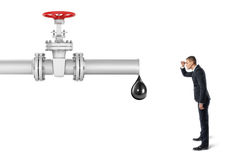 Businessman on white background looking at pipe with red valve that`s leaking one big oil drop. Businessman on white background looking at pipe with a red valve Royalty Free Stock Photos