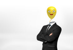A businessman on white background stands with crossed hands and a yellow happy face balloon instead of his head. Royalty Free Stock Image