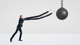 A businessman on white background trying to grab a wrecking ball with his extremely long arms. Grab your freedom. Ball and chain. Business obligations Stock Photos