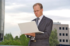 Businessman with white laptop outside Royalty Free Stock Photo